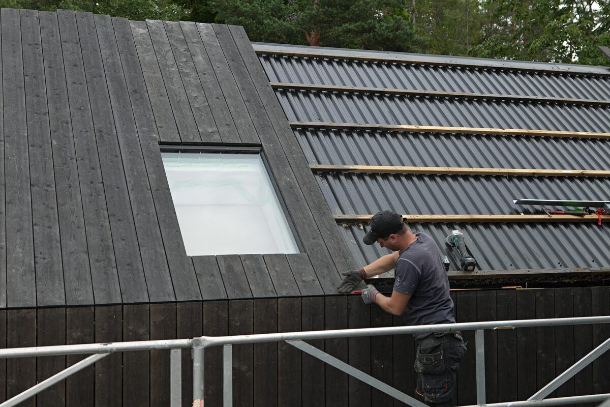 Aivis Bygg working on a modern wooden roof
